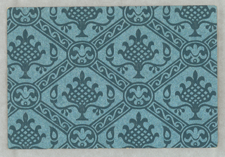 Tekko. Blue paper embossed to simulate damask. A shiny surface. Diagonals cross, enclosing a fruit or plant form. Small scale.