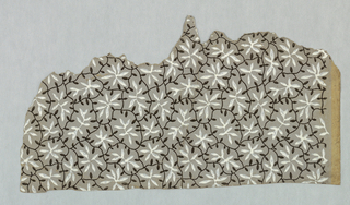 Small leaf forms enclosed in irregularly-shaped compartments formed by vine-like streamers. Printed in white and black on gray ground.
