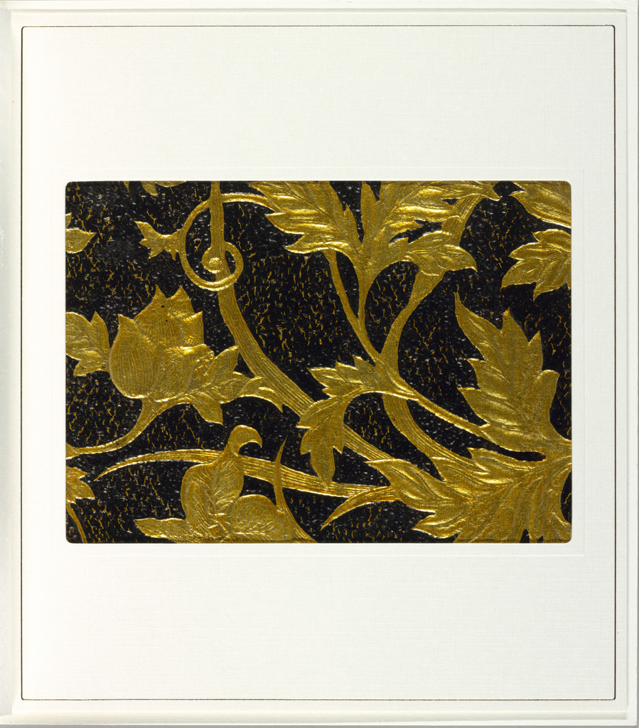 Embossed foliage and flowers, printed in gold, against a textured black background.