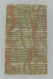 Loosely woven green fibers with rust-color thread on a metallic green support.