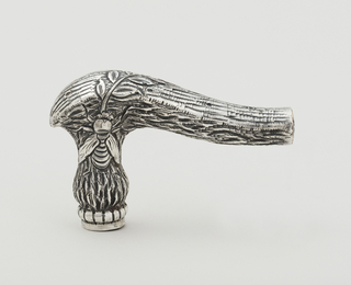 Upper part of umbrella stem in the form of a gnarled branch with pricked symbols on edge, with slightly flaring repousse silver handle with four floral panels and a foliated cap.