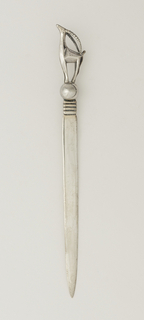 Letter opener with finial in the form of a gazelle perched on a ball.