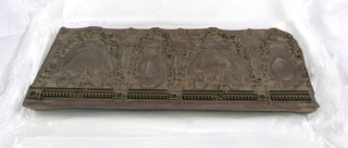 Rectangular block consisting of five layers of laminated wood, of which the upper is carved. Shaped brass plates and pegs provide the highlights for a pattern with four-scalloped drapery, produced from woodblocks 1956-164-1 and -2.
