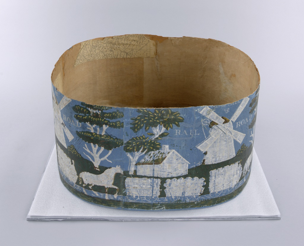 Wooden bandbox, lid missing, covered with block-printed wallpaper. Horse-drawn railroad cars, trees, and windmill printed in white, dark green, and brown, with yellow highlights on blue background. Lettering in white: WINDMILL & RAILROAD. Interior lined with plain paper, patched with bits of maps.