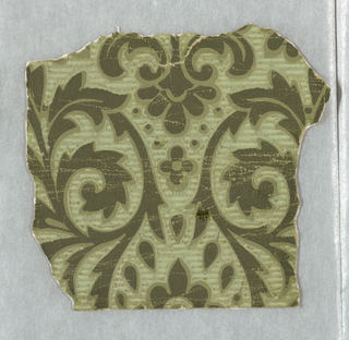 Small portion of a paper showing a symmetrical arrangement of foliage rinceaux. Printed in greens on green ground.