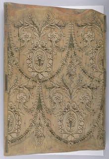 """Vertical rectangle with irregular short sides. Basic block for multicolored design, cut for larger printing areas. Leafy swags (the stems and a few nails in brass), containing wreathed oval medallions with flower. At junction of swags, two crossed flutes in laurel wreath. Drop repeat, drop match. Block stamped """"8596""""."""