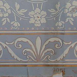 Delicate urns and floral ornament with foliate band running along the bottom edge.  Printed in white and gold on a background that fades from medium blue at the bottom to a pale blue at the top.