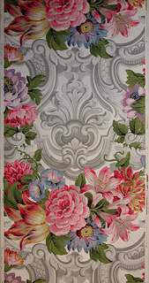 Full width with more than one repeat of design composed of rococo scrollwork in grisaille set with large floral clusters in color. Printed in colors on glazed white paper.
