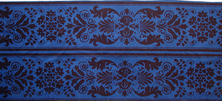 Dark brown floral pattern on royal blue, consisting of paired acanthus leaves framing antifix with lily-of-the-valley and small blossom group between. Design set off with heavy border lines. Straight repeat.