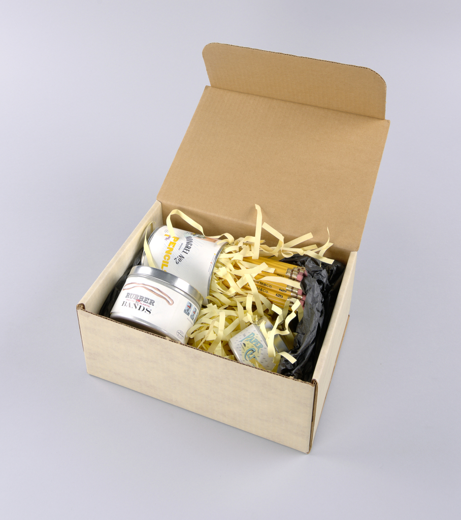 White corrogated box includes the following: pencil tin with white label, filled with pencils;rubber band tin, filled with rubber bands; paperclip tin, filled with paperclips.
