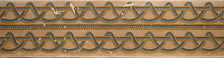 Double interlace of cables. Printed two across with another single band separating. Resembles fancy gimp. The top border is shorter in length. Printed in blue, yellow ocher and brown on a tan ground.