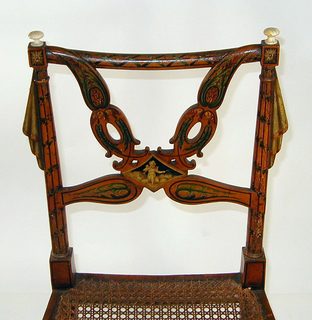 The chair's caned seat is rounded at its corners.  Its openwork back has drapery swags joined by small diamond-shaped medallions painted in black and white with cherub figures.  The legs taper and are painted with vertical lines and foliage; the back supports are similarly decorated and have ivory finials.