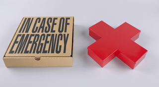 """Red Cross Box: Cardboard box, written on top, """"In Case of Emergency"""" Contains cross-shape red tin box"""