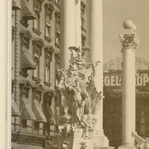 Photograph of the Dewey arch at Madison Square. The arch is flanked on either side by a colonnade and people are walking in the center.