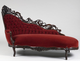 Serpentine front, rounded ends, cabriole legs fitted with castors; back of serpentine profile, raised high in circle at one end and crowned with pierced cresting of laminated wood in scrolls and acanthus shoots. Cluster of flowers in relief at center of arched back, and another at center of apron. Upholstered in contemporaneous machine-woven fancy compound satin, tufted on back.
