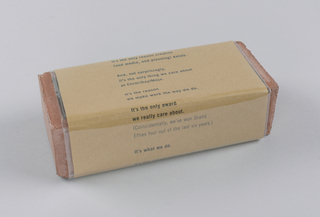 In the present object, a promotional piece for the Chiat/Day agency, a rectangular brick in the standard brick reddish-brown color is molded with a raised border,  enclosed on its four long sides in a brown paper wrapper, and tied with pale beige twine.  Brick - Recto: Chiat/Day/Mojo is incised in raised upper and lower case letters from left to right across the center. Verso: Effective is incised in raised upper case letters from left to right across the center.  Wrapper - Recto:  In upper and lower case, beginning close to the top edge, occupying three quarters of the page length, and centered side to side, a sequence of brief paragraphs, ranging in length from one to four sentences, comprises a statement of the Chiat/Day advertising philosophy.