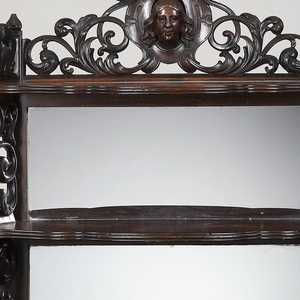 Table is oval half-round in shape, supported on four scroll legs. Curved stretcher with openwork crest. Shaped plinth surmounted by two shelves of graduated size with shaped profile edges, supported on pierced fretwork brackets. Back of two upper shelves fitted with mirror glass. Top of second shelf surmounted by scrollwork with central escutcheon and high relief female head. Finial above head missing. Central drawer on table front, with front panel carved with arabesques and grape clusters. Interior of drawer of maple, with rectangular brass locking device.
