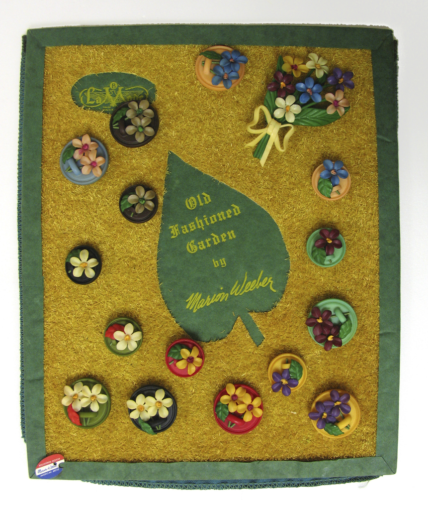 """Upright rectangular card covered in a green felt and cut out of leaf with straw-like material. A green felt border along the edge. 15 circular buttons in green, black, peach, yellow red and blue of various sizes attached to board, with flowers on each button.  Attached is also a brooch of a bouquet of flowers. printed on upper left corner La Mode [logo]; printed in center of leaf """"Old Fashioned Garden""""/ """"by Marion Weeber"""""""