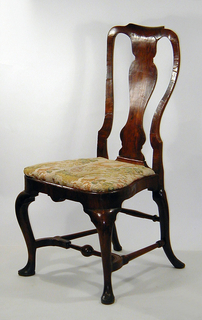 Slip seat. Plain cabroile legs ending in club feet; rounded back, vase-shaped splat.  Seat-rail, shaped, and back are veneered.  Legs joined by stretchers, the front one of turned baluster form.