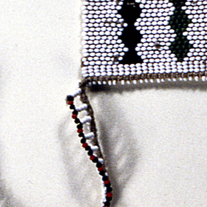"Necklace known as a ""love letter."" Small white beaded squares, each with a multicolored drum, alternate with loops of white and multiccolored beads. The various color combinations and designs convey messages connected with courtship."