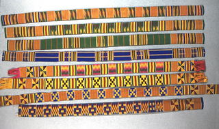 Narrow woven strip with bands of pattern, including stair-steps, interlocking squares, and zig-zags, in black, blue, green, yellow/orange, and dark red.  Patterns are formed by alternating warp-faced plain weave with weft-faced plain weave on grouped warps, two-color complementary wefts, and supplementary weft patterning (brocading).