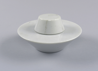 (a) bowl/dish of white marble. Circular shape, tapered sharply inward toward narrow circular base. Upper section with broad rim. Hemispherical depression in center. (b) cover of white marble, circular, tapered toward one end. Flat top and narrow bezel to fit into depression on base.