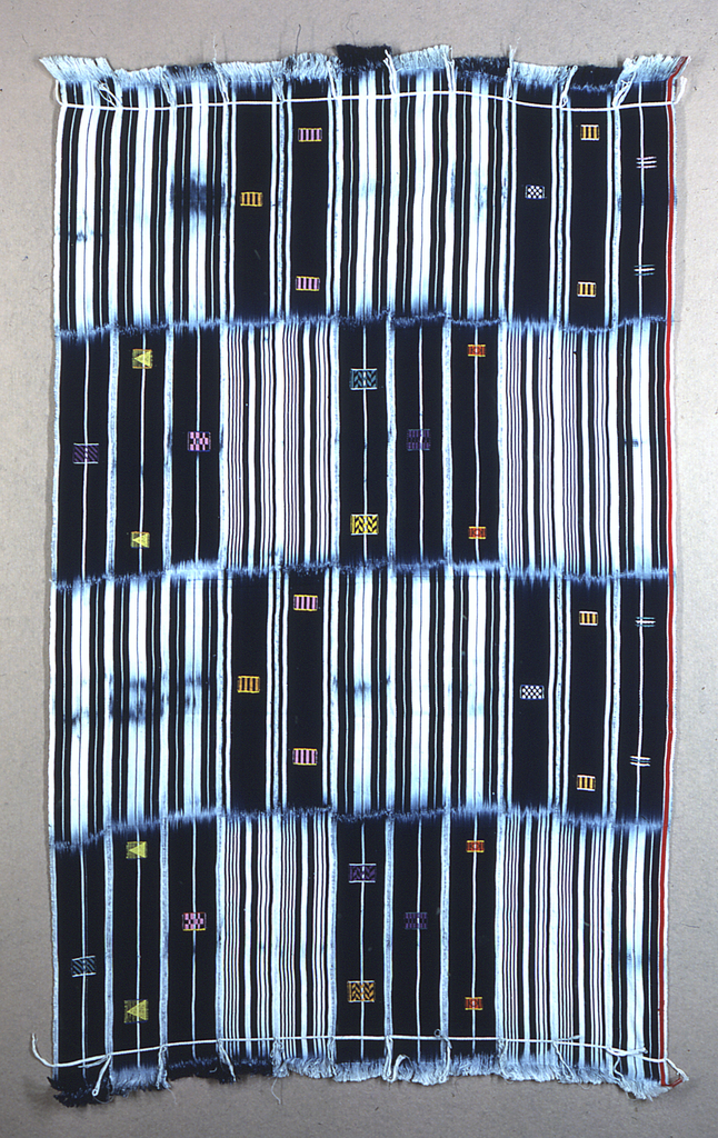 Panel formed of eleven narrow strips, each 3 3/4 inches wide, sewn together. Each strip is patterned by a 17 inch section of narrow blue and white stripes alternating with an equal length section of a wide blue stripes, decorated with small geometric brocaded shapes in bright colors. The strips are sewn together so that the whiter and darker areas form a checkerboard. Red stripe along one long edge. Warp fringed at both ends.