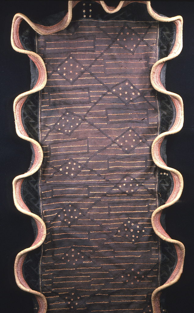 A woman's ceremonial skirt with a center panel of dark purplish-brown, with a design of interconnected diamonds with striped and dotted fillings created by buttonhole embroidery and withdrawn element work. A wide border on three sides has dark brown raffia cut-pile embroidery with interlacing patterns. Also on three sides, a heavy wrapped cord attached with a buttonhole variation in orange raffia, creating a form of ruffled edging.