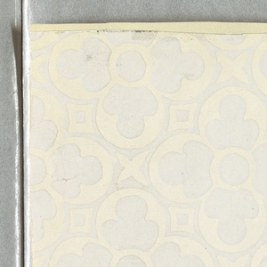 Quatrefoils with enclosed leaf motifs. Printed in white on a white satin ground.