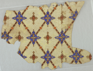 Narrow brown diagonal bands form a diaper pattern at the intersections of which are blue four-pointed motifs resembling stars. At the center of the open spaces of the diaper are brown diamond-shaped figures. Printed on cream ground.