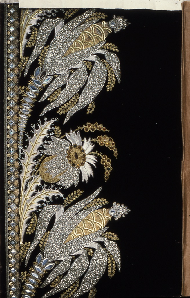 Blue cut velvet, embroidered in border design in gold and silver thread, flat silver paillettes and white and orange glass brilliants. Pattern worked in relief suggests wheat or corn thistle and leaves.