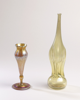 """Iridescent yellow, slightly opaque on neck and shoulder, clear at base. Tall slender neck with small lip. Central portion of the body indented tripartitely, bottom portion is flattened sphere. Incised marks on base: """"T 4550 L.C.T. Favrile"""""""