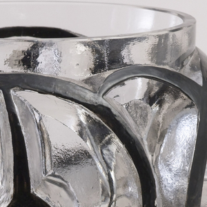Broad tapering cylindrical glass body, its deep wall carved and etched with a continuous pattern of swirled lines, their surfaces highlighted in black enamel.