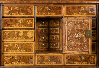 Cabinet on stand with floral marquetry veneer. Cabinet fronted by two large doors with brass lock plates that open to reveal twelve small interior drawers, each with brass pull, and one cupboard door with brass lock plate, all veneered with floral marquetry. Long narrow drawer in cornice molding on top. Stand has long narrow drawer with two brass pulls and one lock plate, supported by six scrolled legs with curved stretchers and bun feet with metal casters.