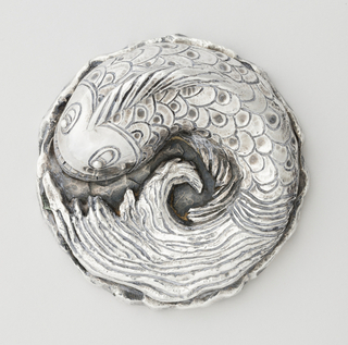 Flat, irregular disc in form of curled fish. Head has wide mouth with 2 rows of teeth and bulging eyes. Body has scales inscribed on it and tail inscribed with irregular lines.