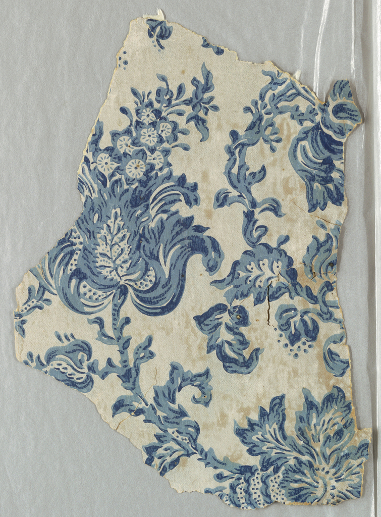 Irregular fragment of paper with freely drawn conventionalized flowers, and leaves in two blues on finely granulated off-white ground.