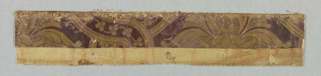 Burgundy background paper with gold pattern of ribbons and flowers. Printed on paper and mounted on muslin