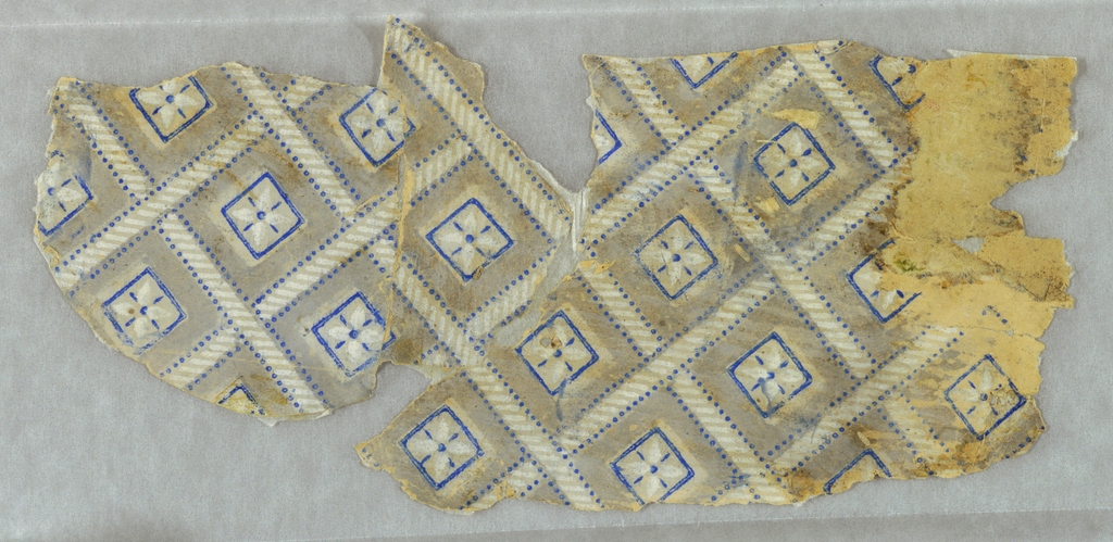 Small diamond diaper design. The grid pattern has the appearance of twisted rope, with blue pin dot edges. Contained with this framework are small squares outlined in blue, with a small floral motif in center. Printed with a gray background.