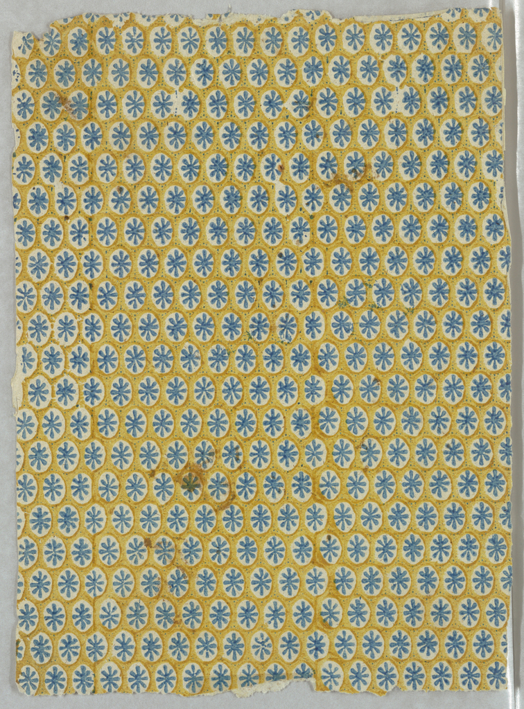 Small-scale all-over pattern of geometric pattern. Blue asterisk-like motif set in mustard-yellow framework, on white ground.