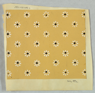 Diagonal rows of flower forms in white, with black centers. Printed in black and white on corn-colored ground.