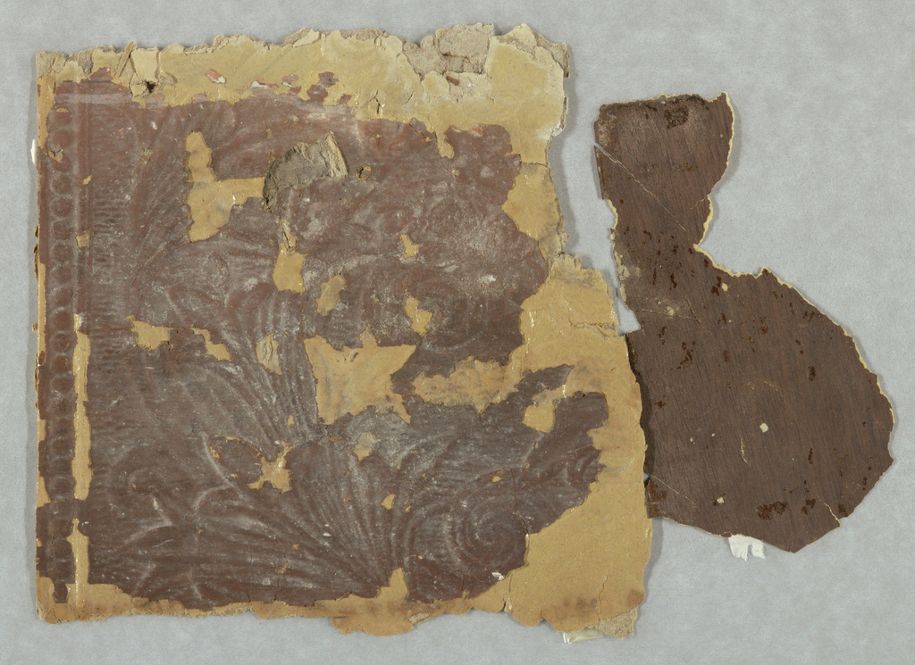 Heavy floral and scroll design of which only a portion is included in this fragment. A bead molding at top. Printed in brown. Adhering to back is brown wood grain paper which probably was used for sidewall.