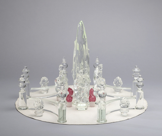 Table centerpiece consisting of 32 glass components and 1 silk undecloth forming a garden with tree in center surrounded by shrubs, figures, and architectural elements.