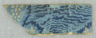 Very small fragmentary piece, appearing to be simulated moire or wood grain design, printed in deep blue, with clusters of small stylized white flowers printed on light blue ground. At one extreme end is part of a wreath of seven-petaled flowers with centers, all in gray. Removed from a bandbox.