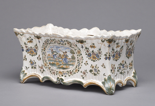 Horizontal rectangular form with everted and shaped rim; base with feet flanking shaped lower edges. White ground with blue, green, and ochre decoration of flowers and garlands surrounding central oval cartouche showing man and woman frolicking in meadow. Opposite side shows a boar hunt scene. Internal supports for missing liner.