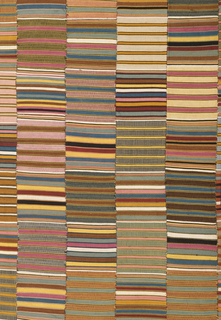 Large cloth composed of narrow woven strips, each horizontally striped in many colors.