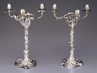 Three branched candelabrum in form of an oak tree. Base outlined by three reverse curves; column represents a tree trunk (from which the lower branches have been cut) with leaves at the top and four twisting branches; three of the branches have acorns serving as sockets for candles. The section above the leaves is removable.