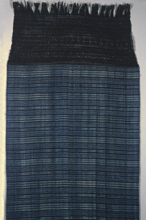 Indigo blue ground with very small spots of white and light blue jaspeado (ikat) patterning in horizontal bands. Elaborately knotted fringe 14 inches deep.