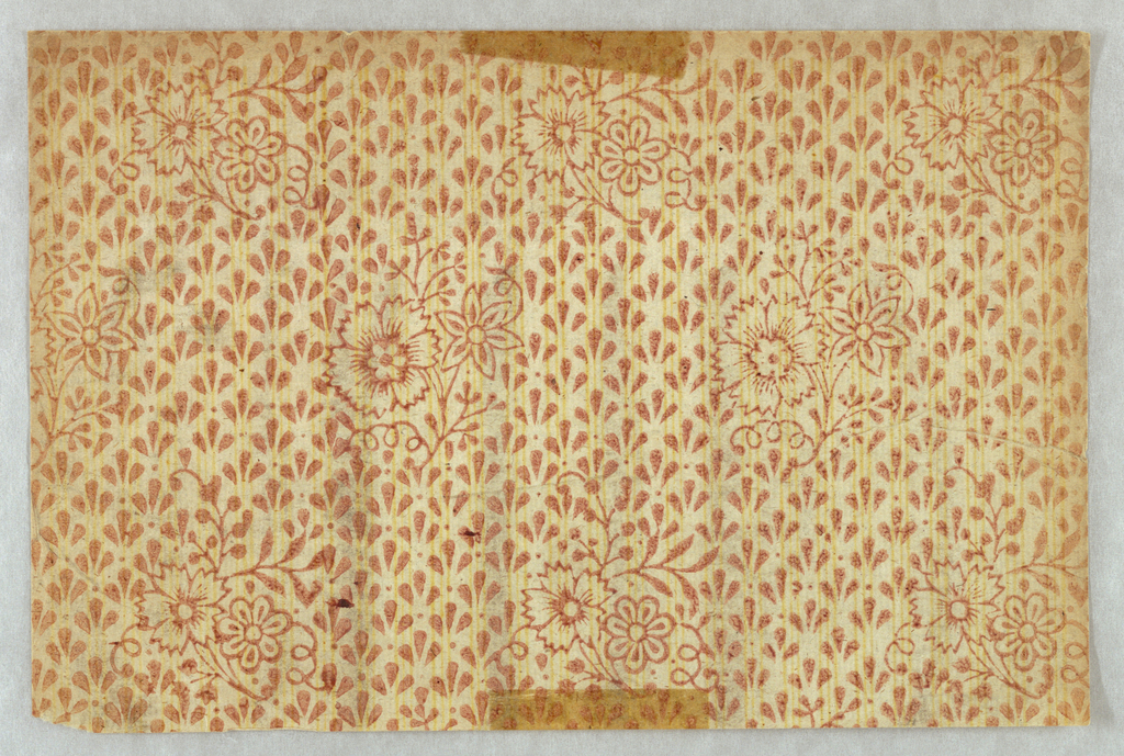 Small floral bouquets surrounded by diagonal rows of petal or leaf motifs, arranged in groups of three. Behind this are thin yellow lines, also in groups of three. The paper is very thin and has a glossy look, similar to book paper.