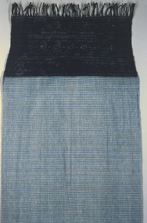 Indigo-dyed in small spots of white and light blue set between thin stripes of navy blue. Dark blue warp fringe 16.5 inches deep with elaborate knotting in rosette, band, and zigzag pattern.
