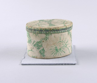 Very small oval-shaped bandbox. Paper is probably wallpaper: chalky-white flowers and leaves picked out in bright green. Small black dots are sprinkled over a portion of the design. The cover is edged with a fluted design, shaded with dark gray.